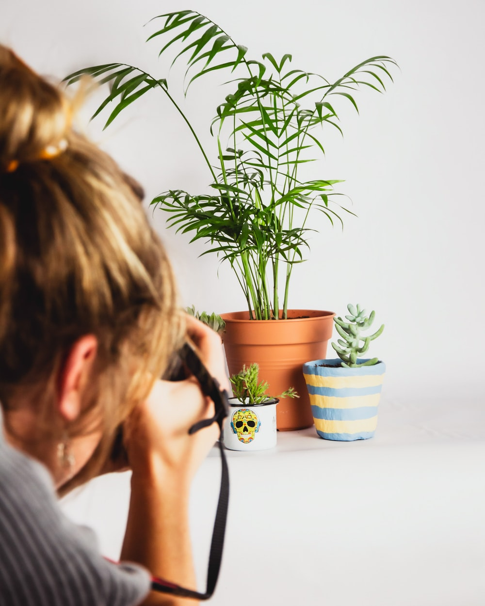 woman in gray shirt holding black ceramic mug with green plant