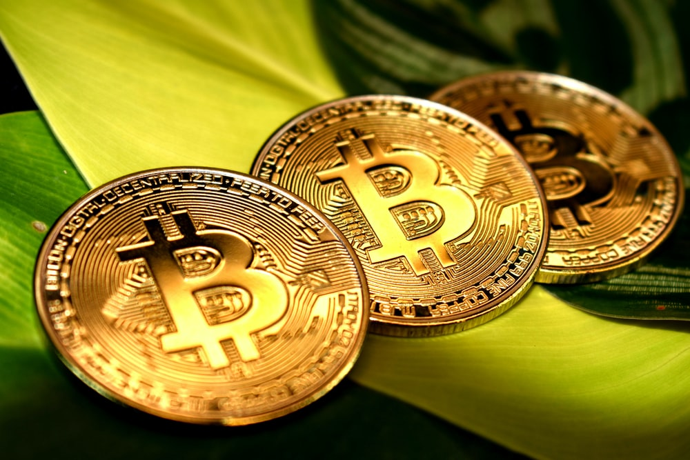gold round coin on green textile