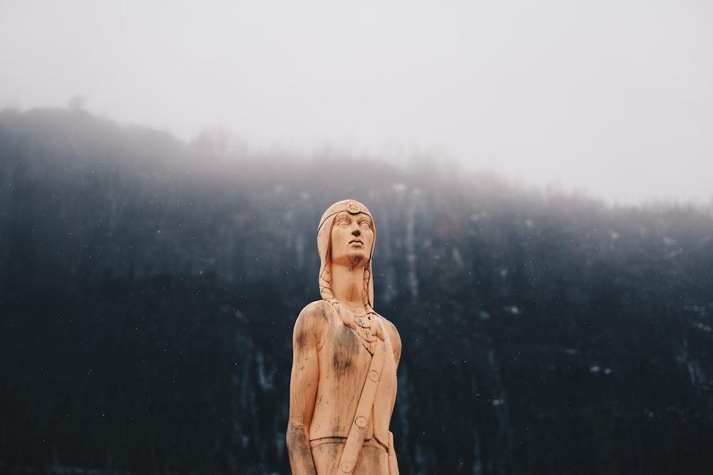 woman in brown coat statue