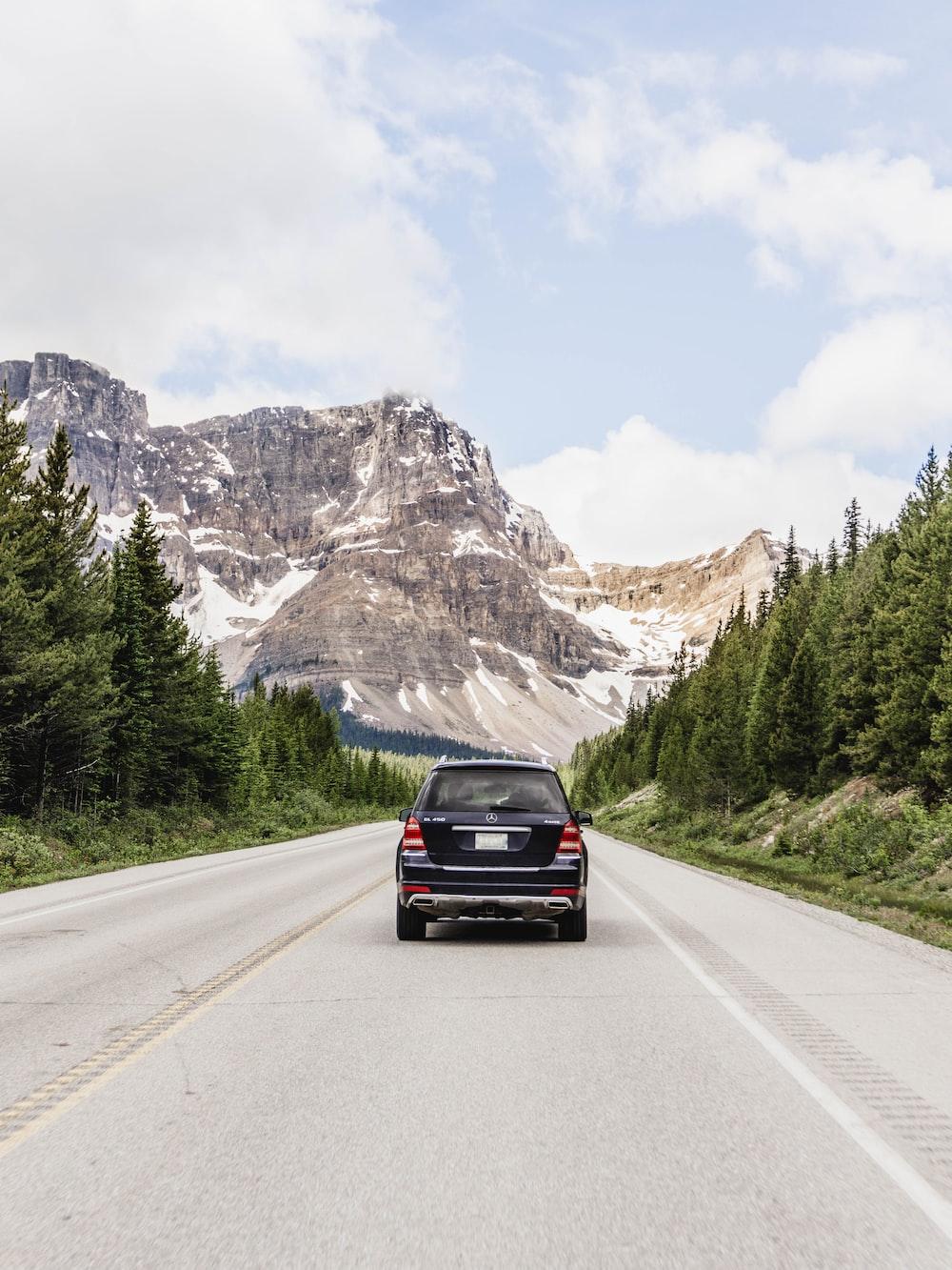 black car on road near mountain range