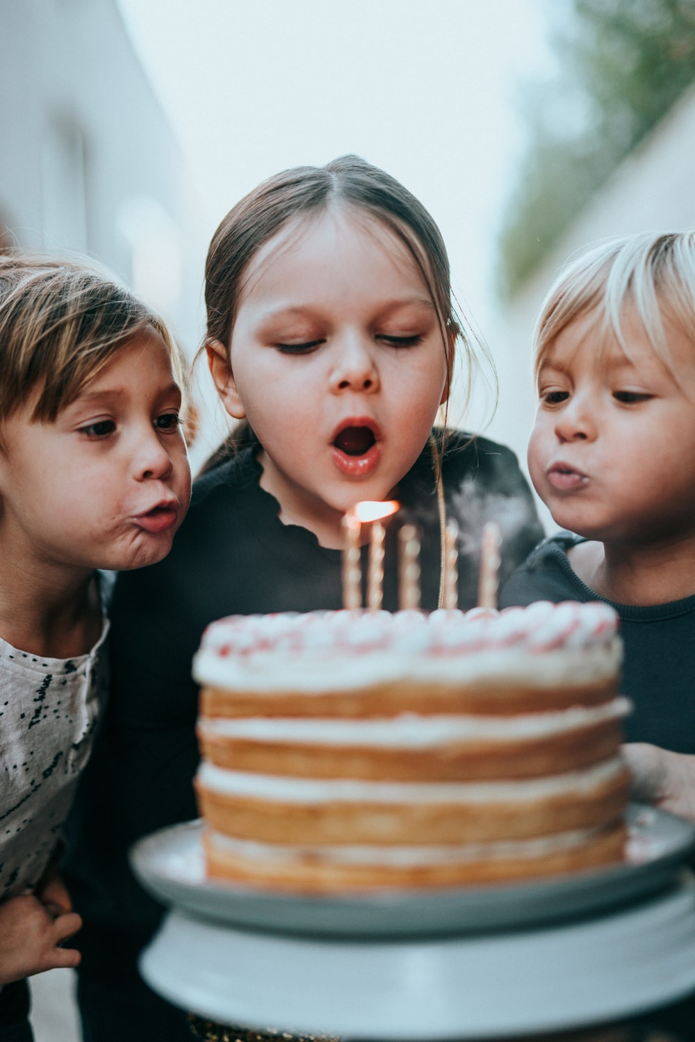 boy and girl blowing candles