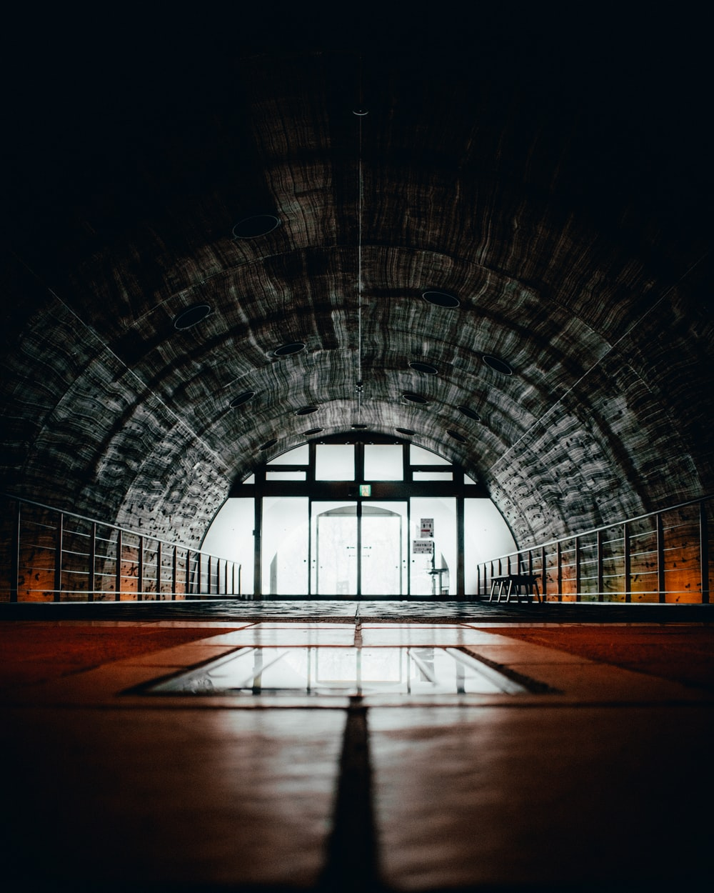 brown and gray tunnel with glass windows