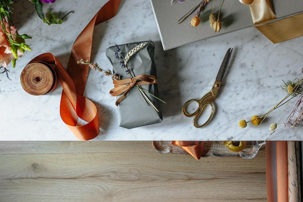 silver scissors beside orange leather shoe