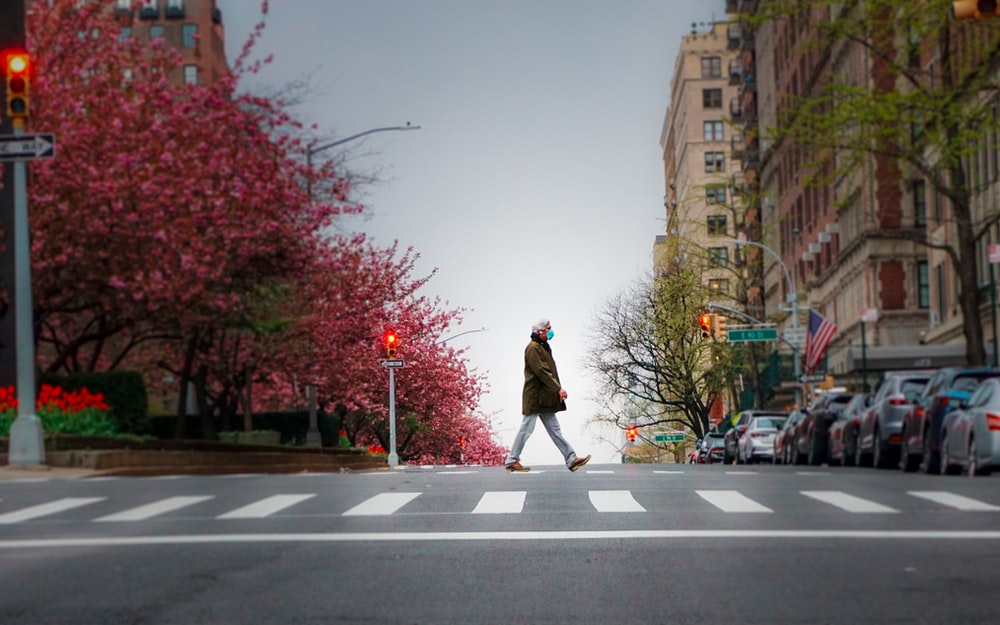 woman in brown coat standing on the road during daytime