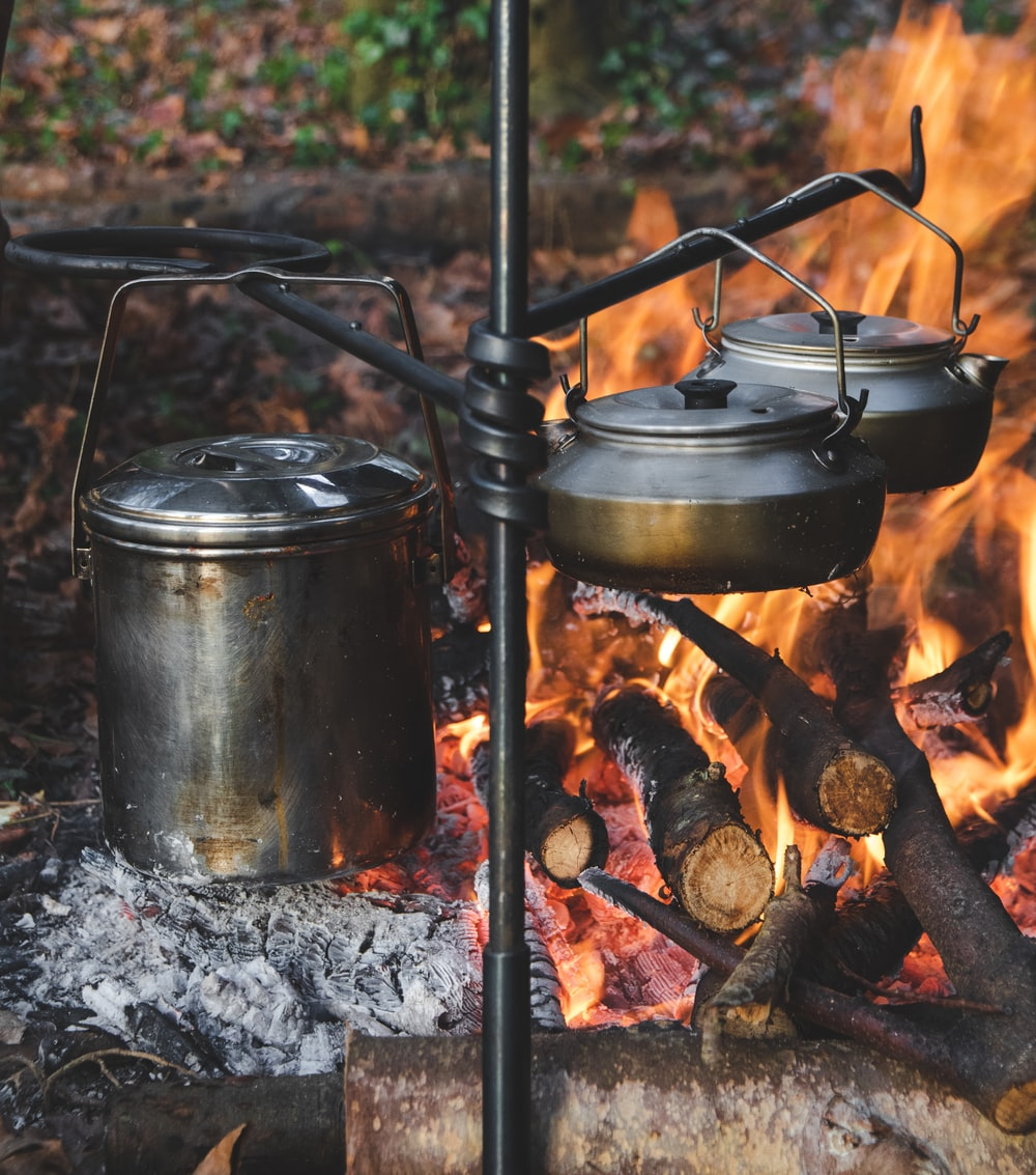 stainless steel cooking pot on black metal grill