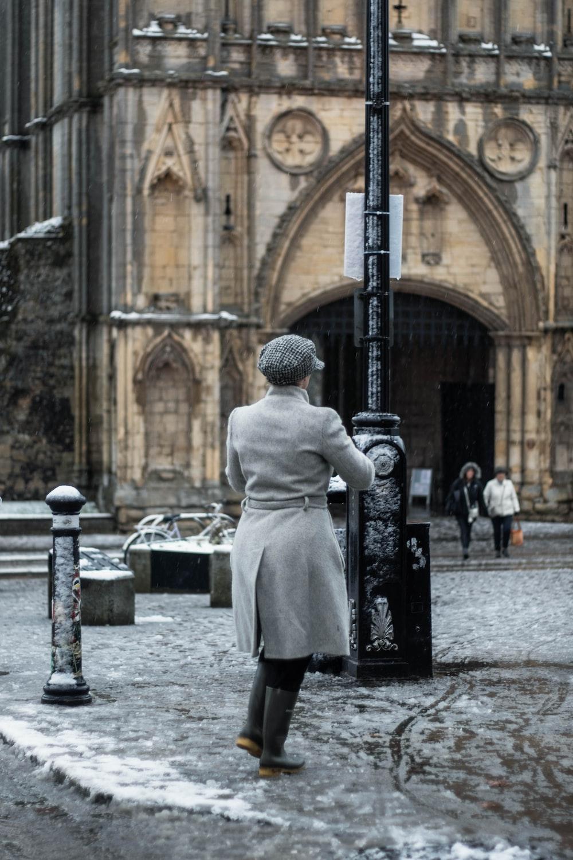 man in white coat standing near black metal post during daytime