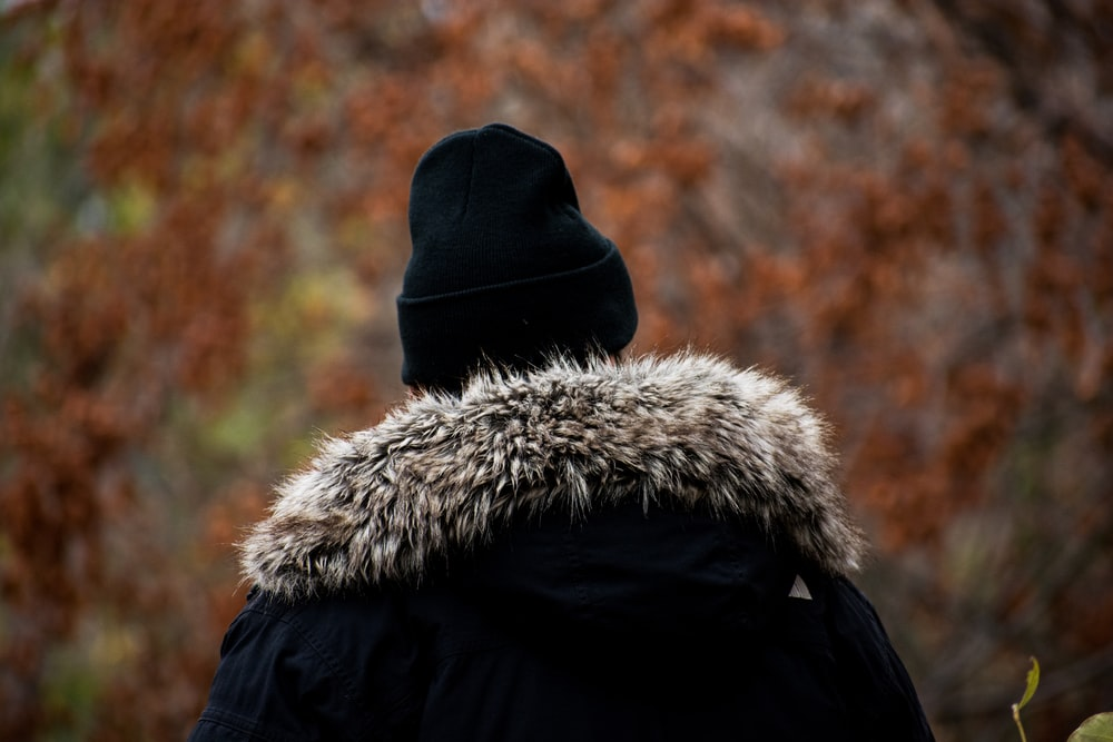 person in black and white fur coat and black knit cap