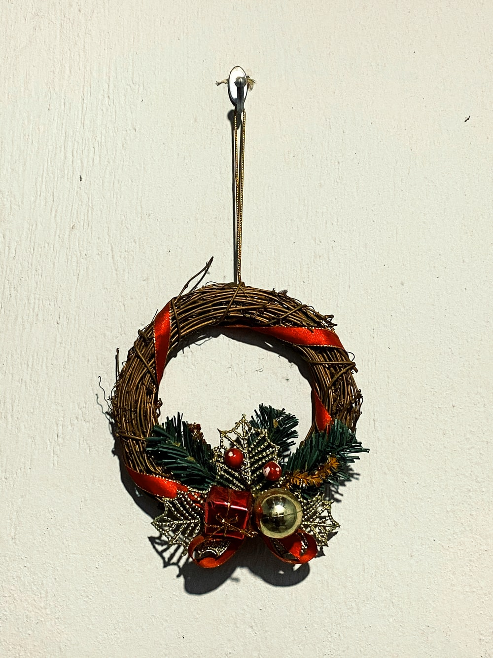 brown and green wreath with red and gold baubles