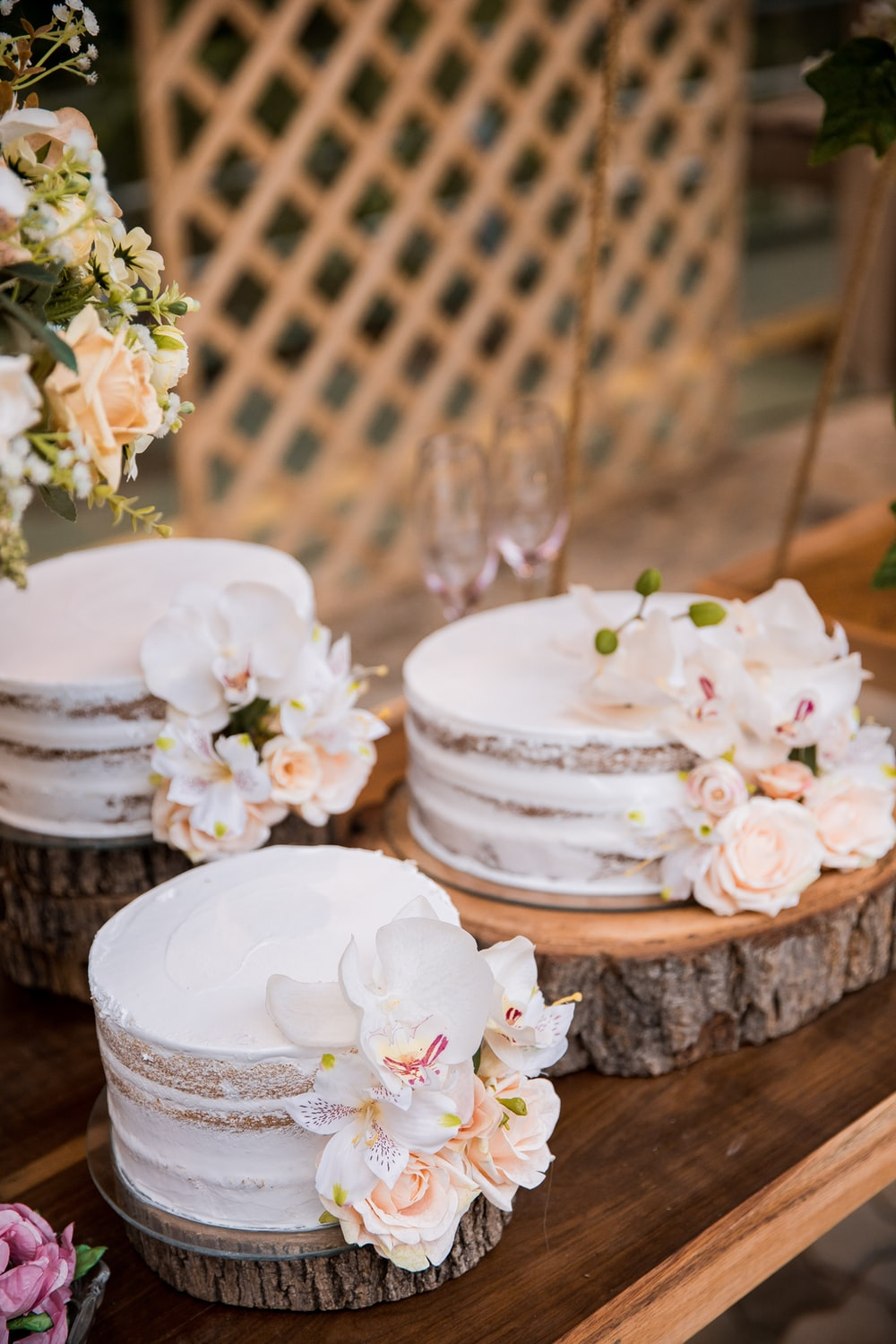 white and pink floral cake on brown wooden table