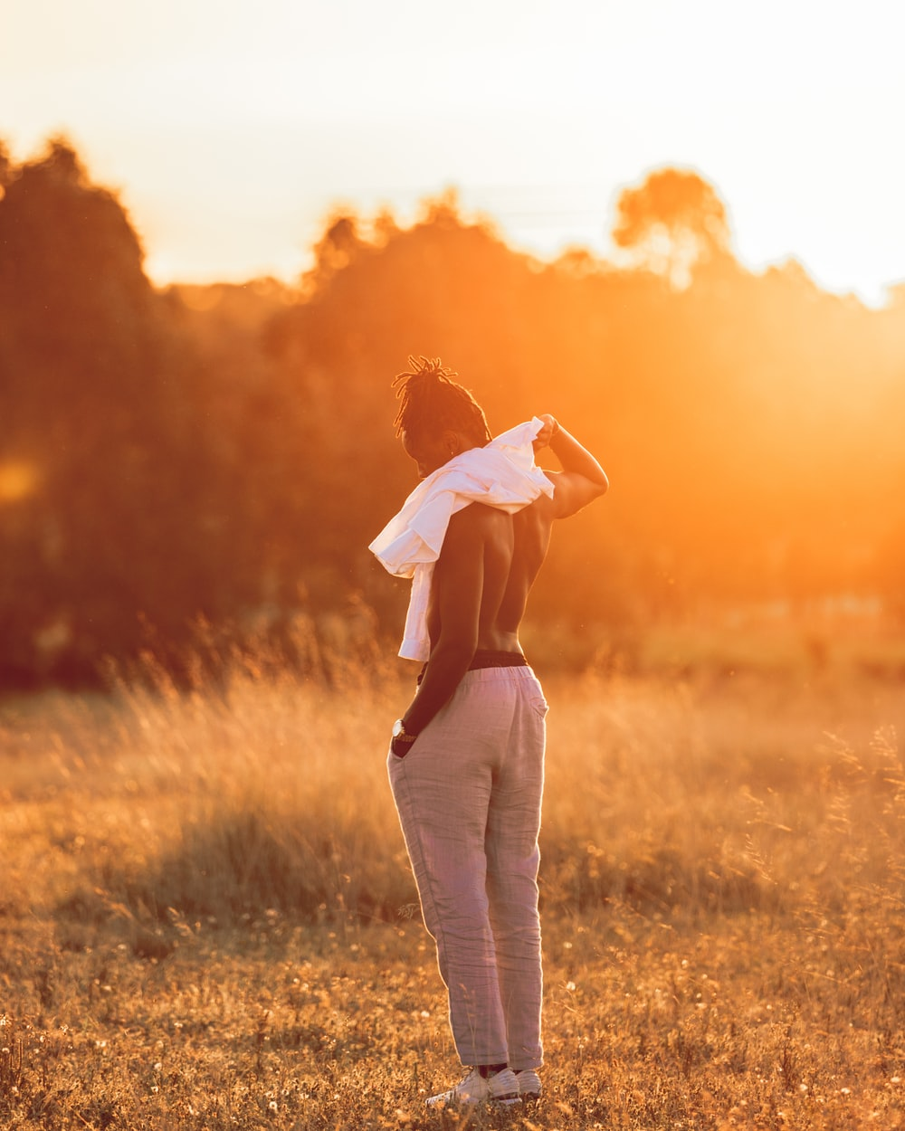 woman in white long sleeve shirt and white pants standing on green grass field during sunset