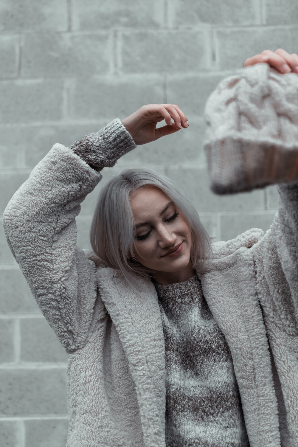 woman in gray sweater holding her hair