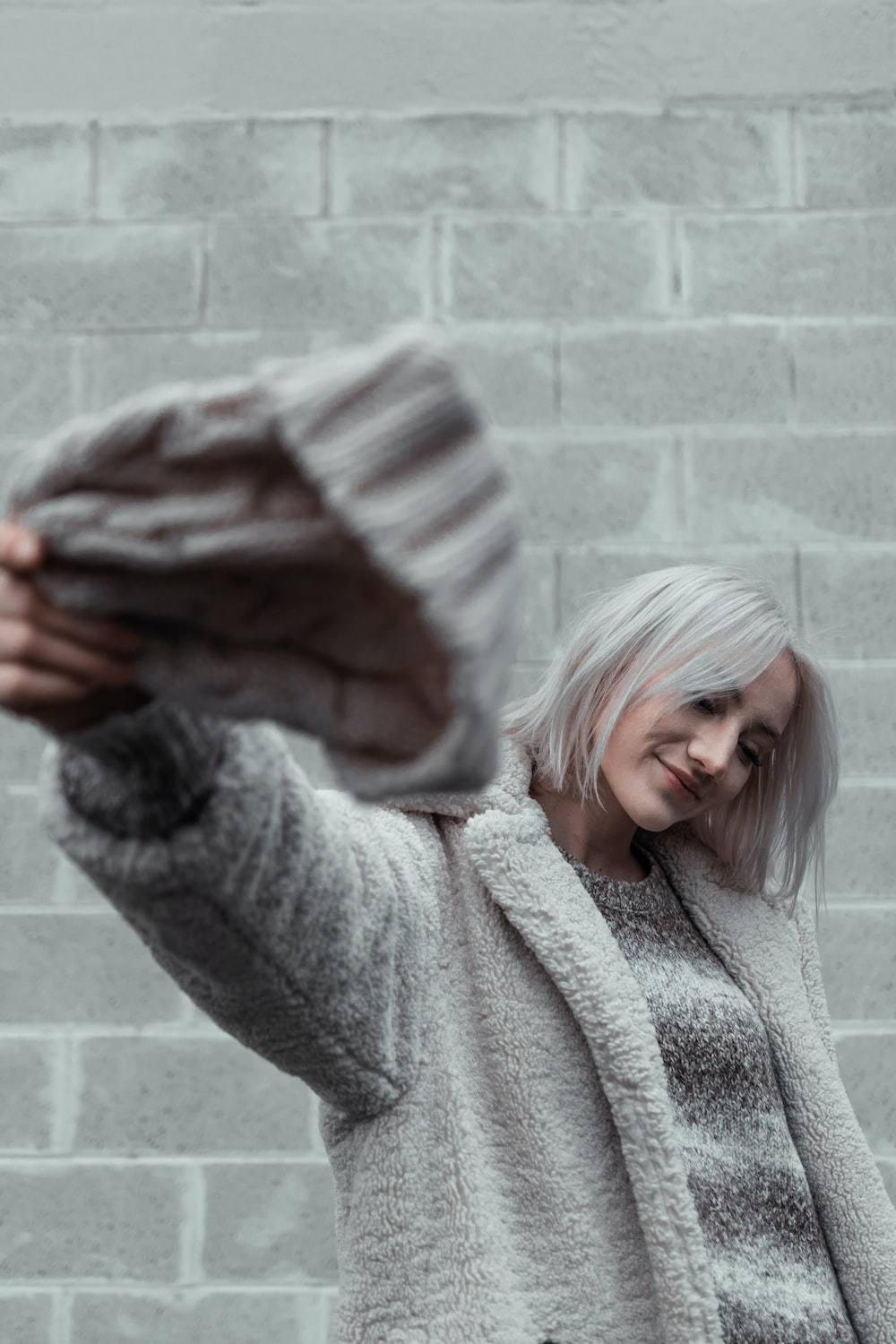 woman in gray sweater covering face with hands