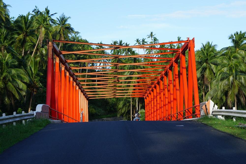 orange metal fence near green trees during daytime