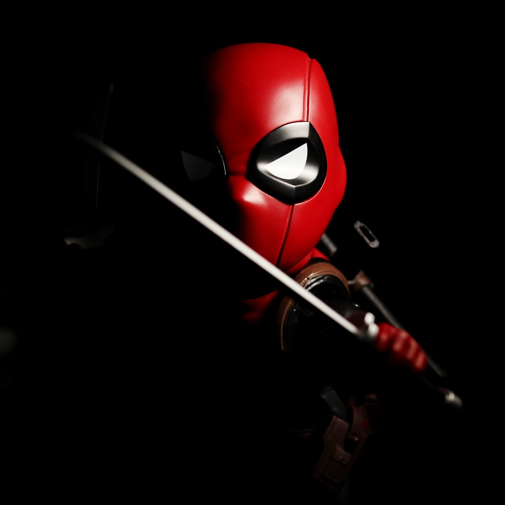red and black mask with white stick
