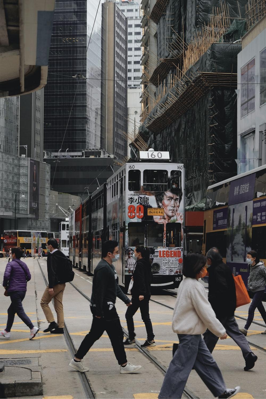 people walking on street near red tram during daytime