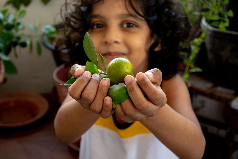 girl in white shirt holding green round fruit