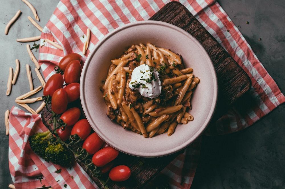 pasta with sliced tomato on white ceramic bowl