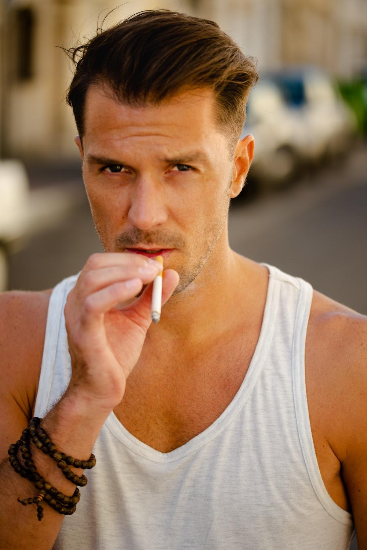 man in white tank top smoking