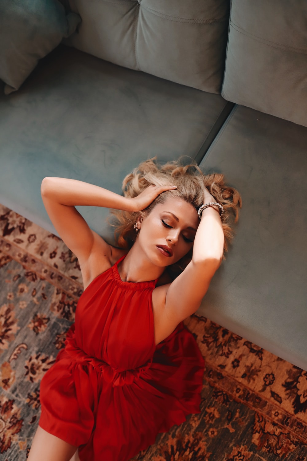 woman in red sleeveless dress lying on brown floral textile