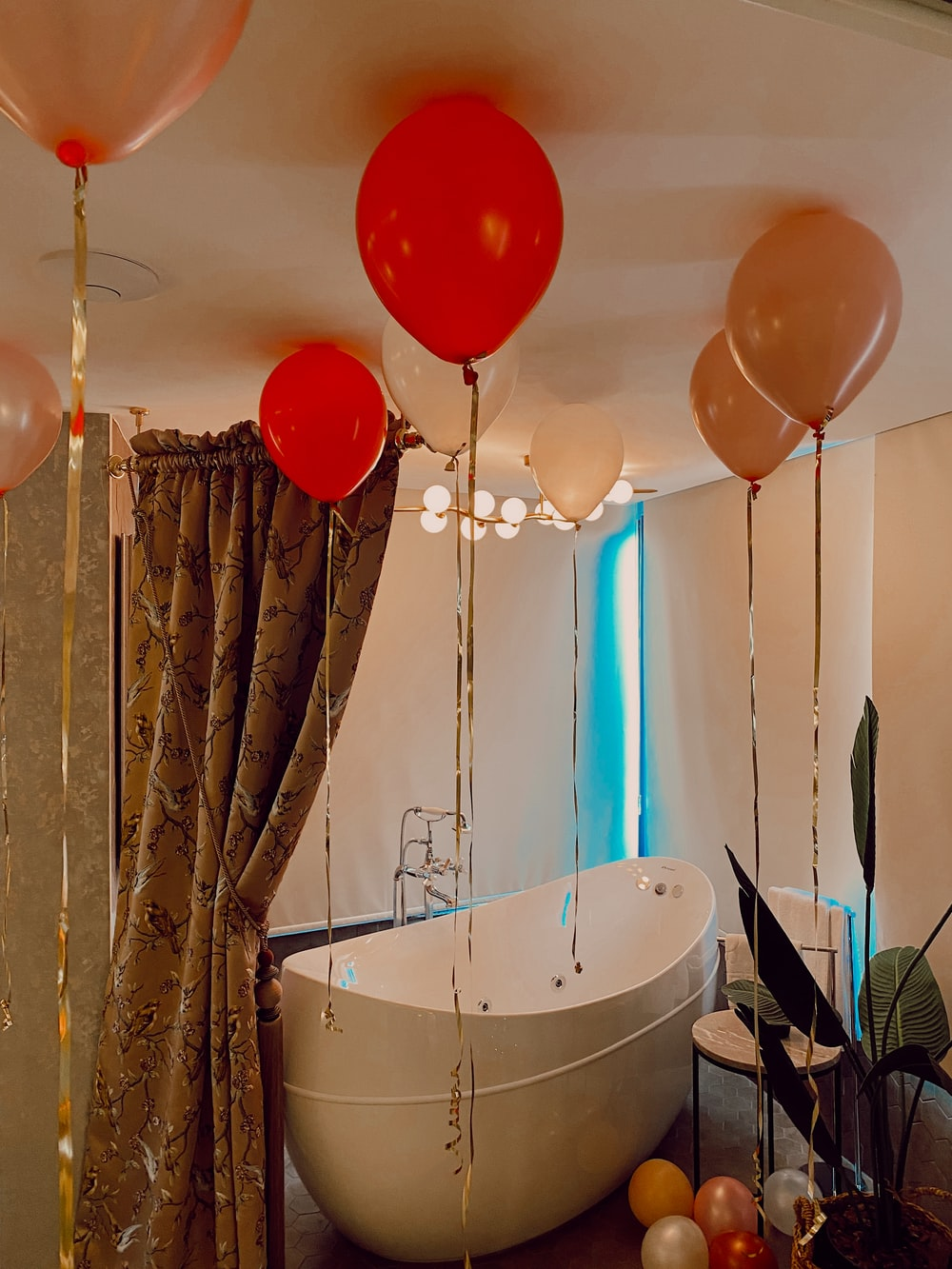 white bathtub with assorted balloons