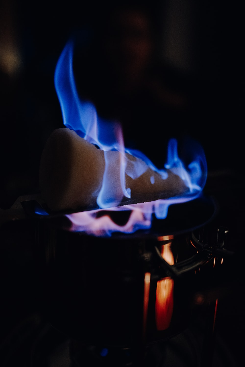blue and white fire in black metal grill