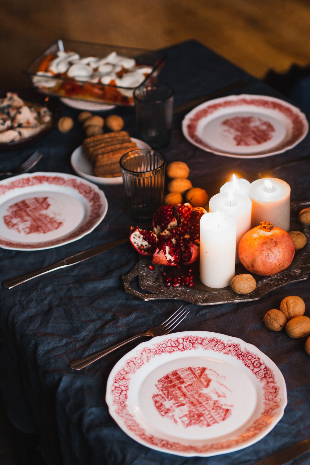 white and red ceramic plate with stainless steel fork beside brown cookies and white candles