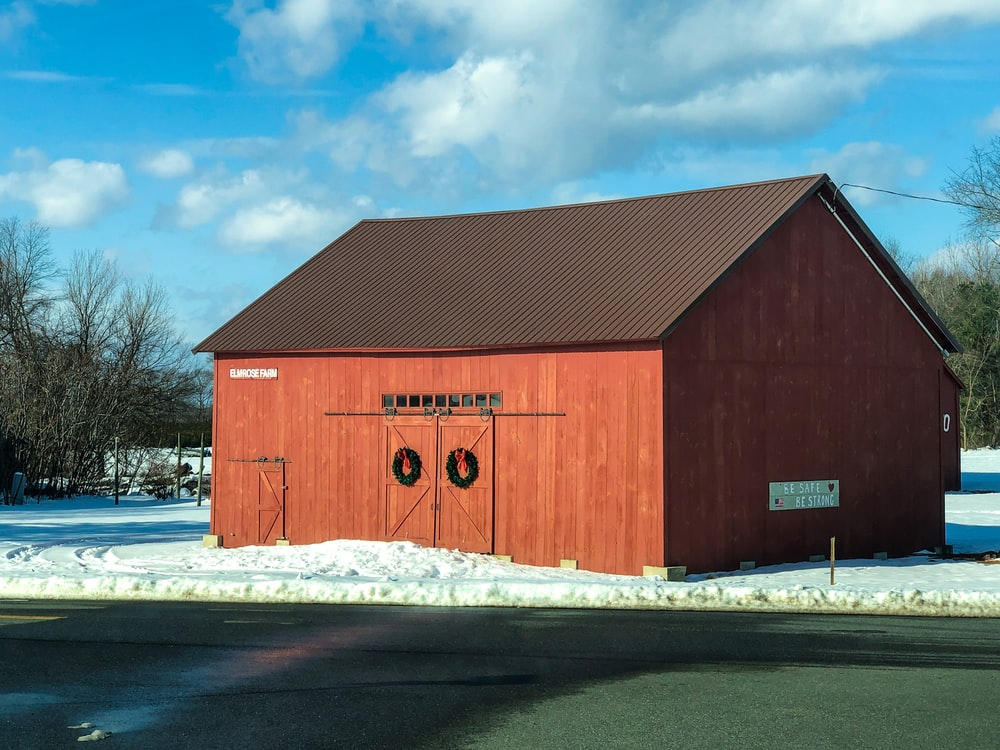 red wooden barn under white clouds and blue sky during daytime