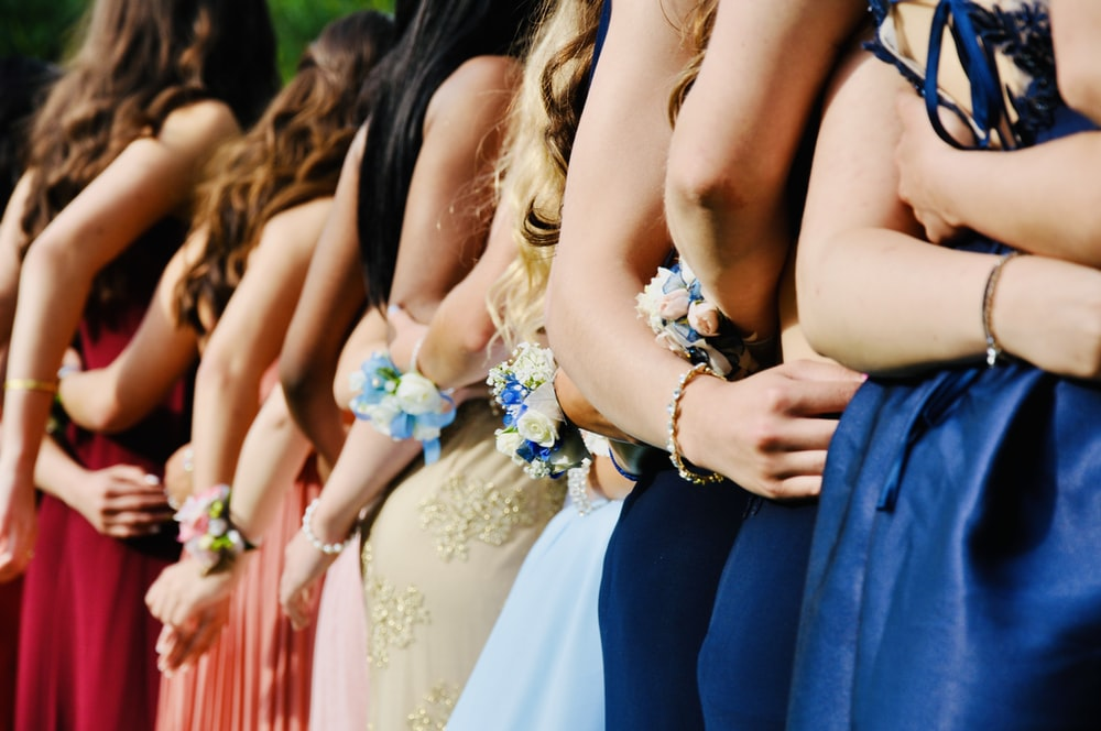woman in blue sleeveless dress wearing blue and white floral tiara