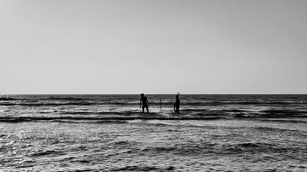 silhouette of 2 person walking on the beach during daytime