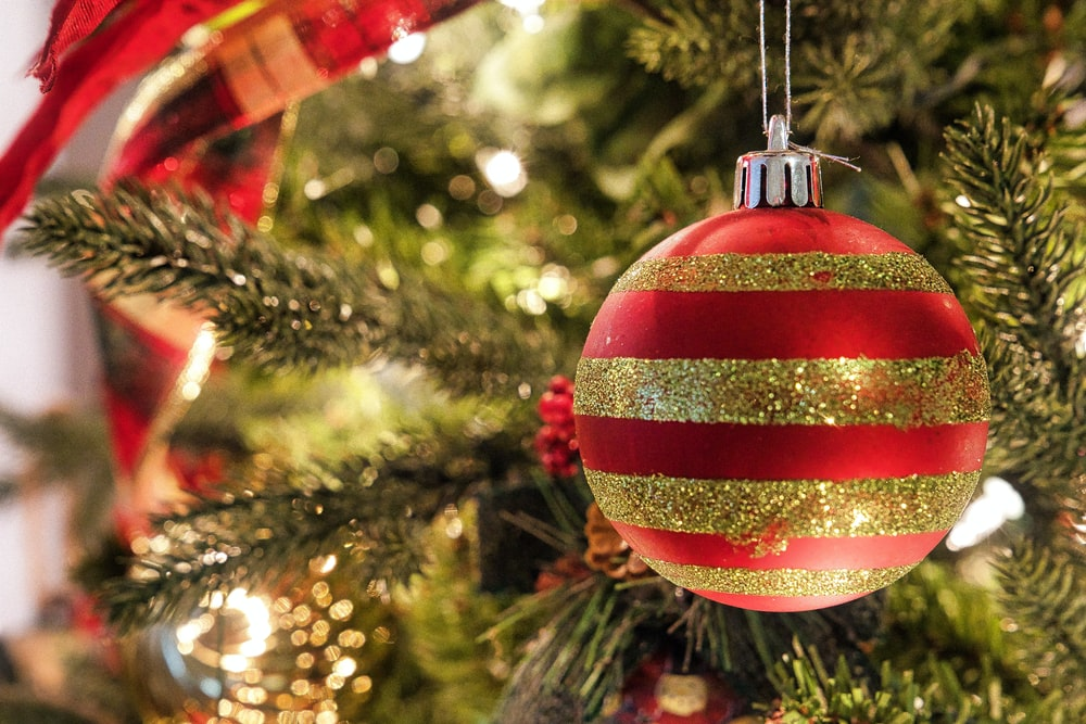 red and white bauble hanging on green christmas tree