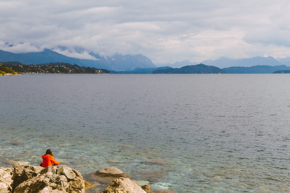 person in orange jacket sitting on rock near body of water during daytime
