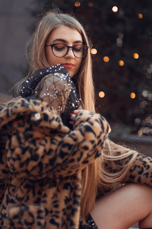 woman in brown and black leopard print coat and black framed eyeglasses