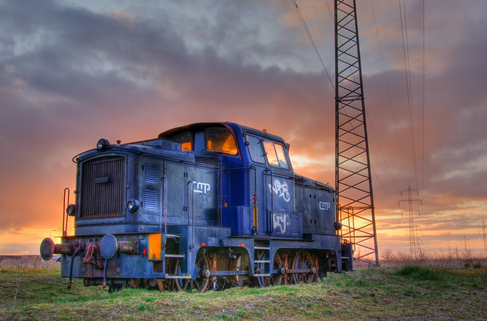 blue and yellow train under cloudy sky during daytime