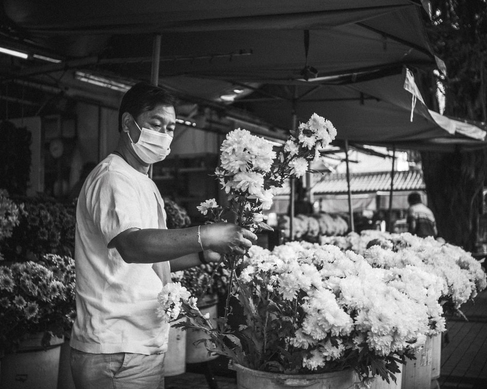 grayscale photo of man in white shirt holding bouquet of flowers