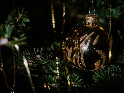 gold and black bauble on green christmas tree