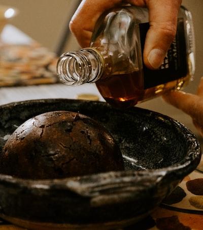 person pouring brown liquid on black ceramic bowl