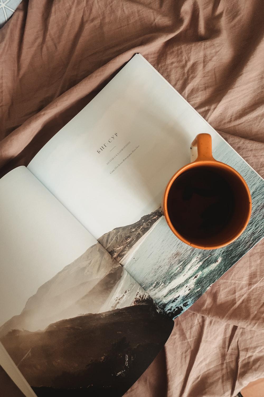 white printer paper beside brown ceramic mug