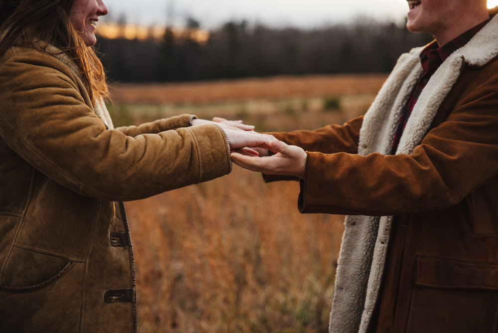 woman in brown coat holding mans hand
