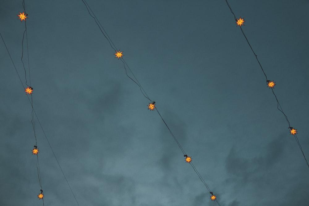 yellow and orange string lights under dark clouds