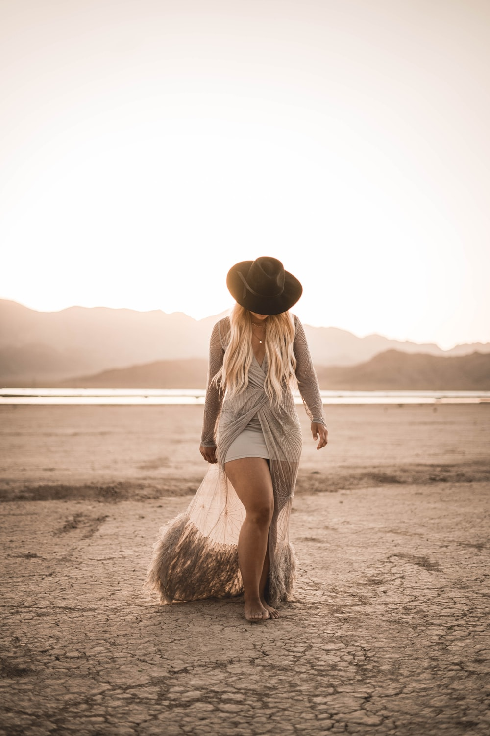 woman in white tank top and white shorts walking on beach during daytime