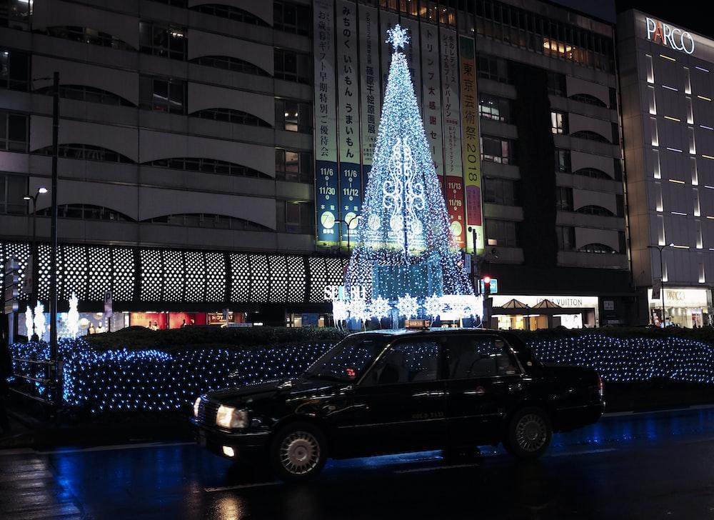 black sedan parked near lighted christmas tree during night time