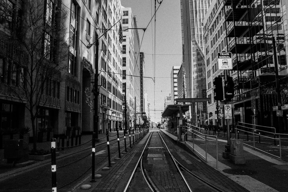 grayscale photo of train rail between buildings