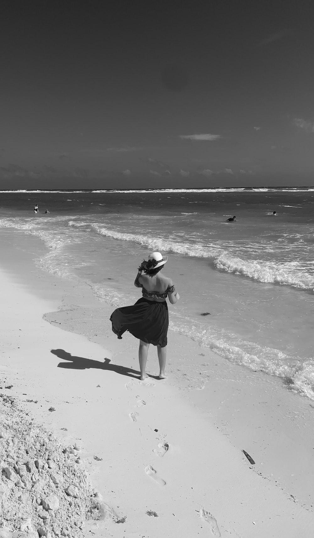 woman in black tank top and black pants walking on beach shore