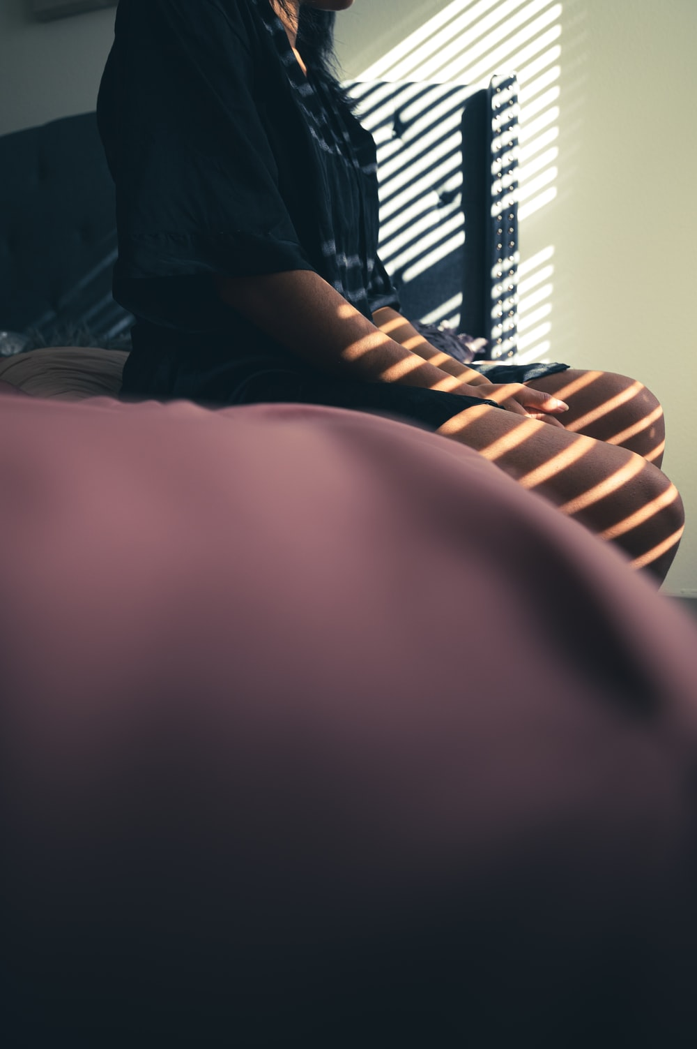 person in black shirt sitting on bed