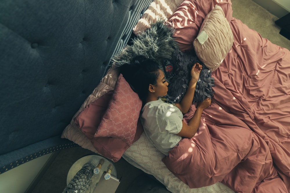 girl in orange dress lying on bed