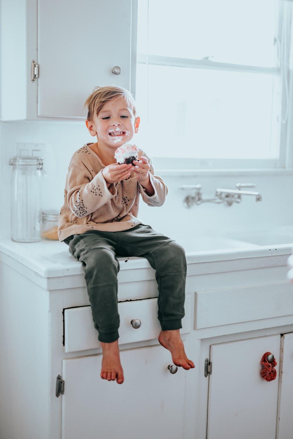 boy in brown sweater sitting on white ceramic sink