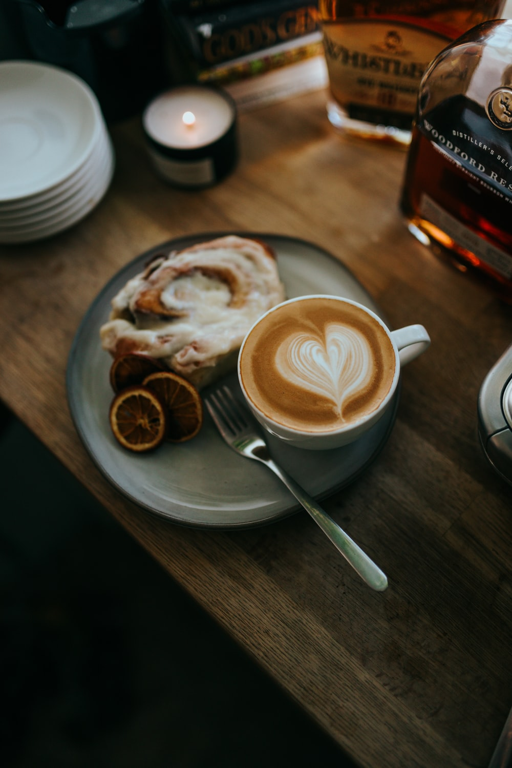 cappuccino in white ceramic cup on saucer beside stainless steel spoon