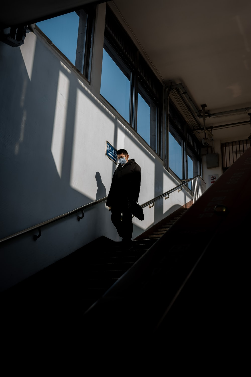 man in black jacket walking down the stairs
