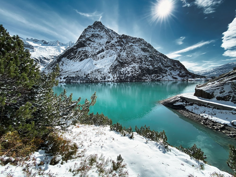 green lake surrounded by snow covered mountains under blue sky during daytime