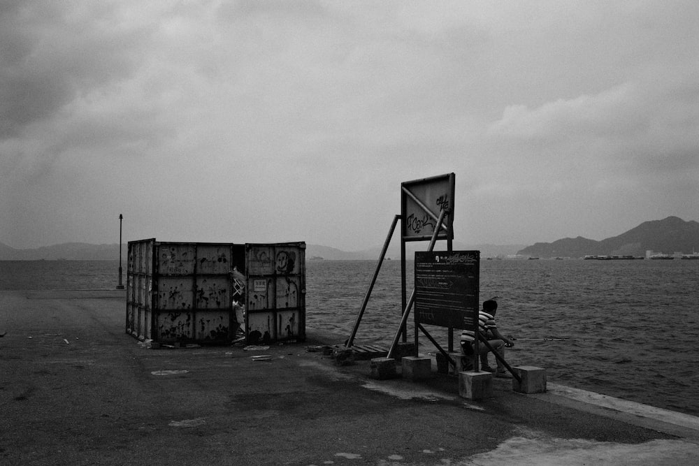 grayscale photo of a black metal frame on a beach